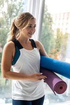 Женский инструктор по пилатесу, держащий коврик для йоги в тренажерном зале возле окна. здоровый образ жизни