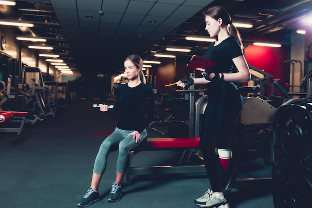 Female instructor giving training to young woman exercising with dumbbell