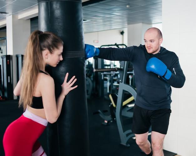 女性インストラクターがサンドバッグを保持し、ボクサーの男性を訓練します。若いカップルのトレーニング