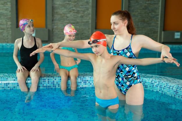 Женщина-инструктор обучает группу детей плаванию в закрытом бассейне.