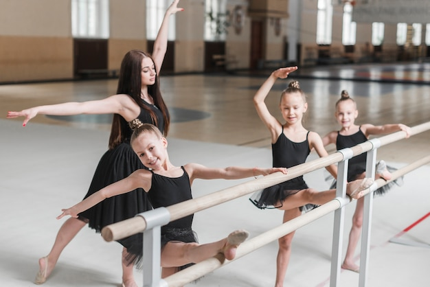 Female instructor teaching ballet dance to girls