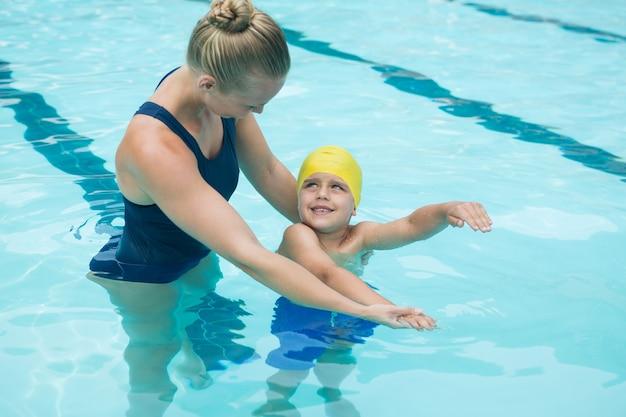 Женский инструктор тренирует молодого мальчика в бассейне