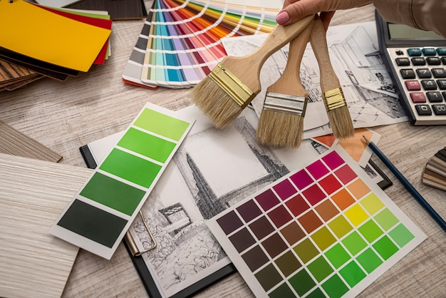Female interior designer chooses color from the palette, working with house sketch at office