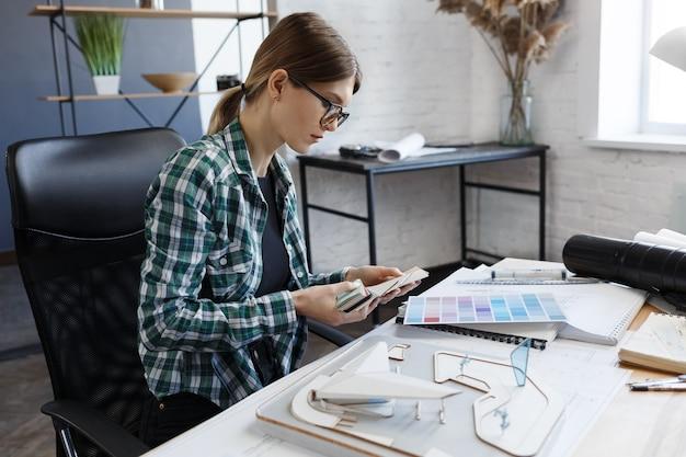 Женский дизайнер интерьера, работающий в офисе с архитектором цветовой палитры, выбирает цвета для строительства ...
