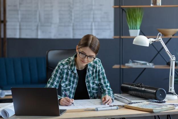 Женский дизайнер интерьеров, работающий в офисе с архитектором-ноутбуком, продумывает архитектурный план ...