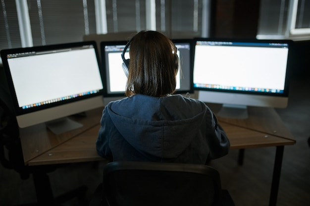 헤드폰에 여성 인터넷 해커는 어두운 사무실에있는 컴퓨터에서 작동합니다. 직장에서 불법 웹 프로그래머, 범죄 직업. 데이터 해킹, 사이버 보안
