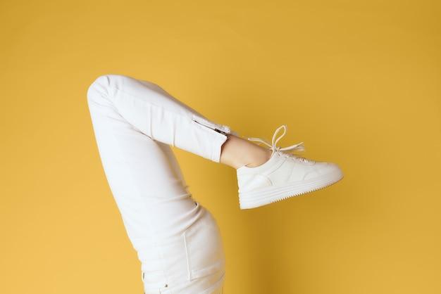 白いスニーカーの女性の逆さまの脚は、黄色の背景をトリミングしました