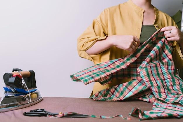 縫製工場での女性のアイロンがけチェック柄生地