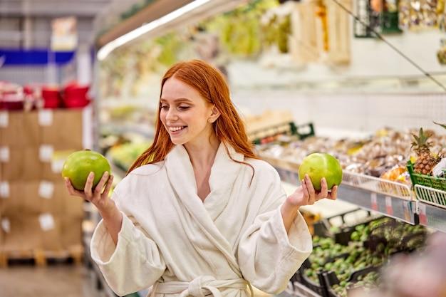 Женщина в халате выбирает свежие овощи и фрукты в магазине. молодая женщина покупает еду в продуктовом супермаркете