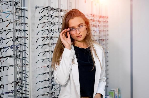 여성은 안경점을 배경으로 원시 안경을 들고 서 있습니다. 안경을 쓰고 서십시오. 시력 교정. 안경을 쓴 소녀가 카메라를 향해 포즈를 취하고 있습니다.