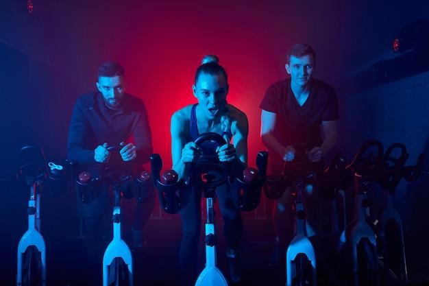 女性は男性スポーツマンと一緒にジムで自転車のマッシングをトレーニングしています。中央の女性は運動をしており、有酸素トレーニングを行っています。