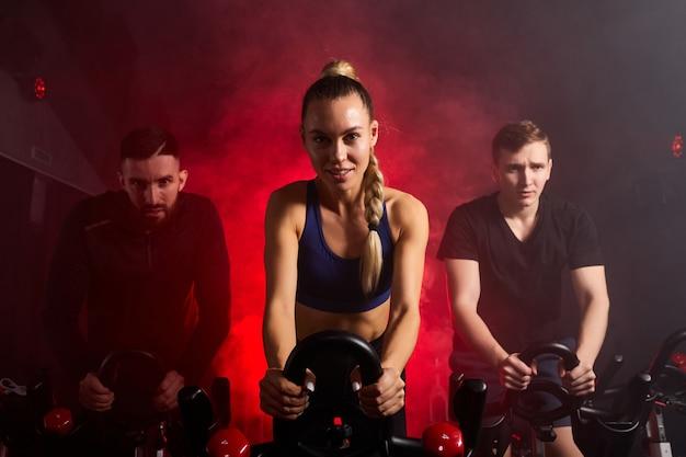 Женщина тренируется со спортсменами-мужчинами на велотренажере в тренажерном зале, гемале в центре тренируется, делает кардио-тренировки