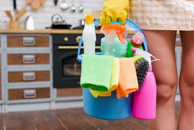 Female janitor holding cleaning accessories in bucket standing in kitchen