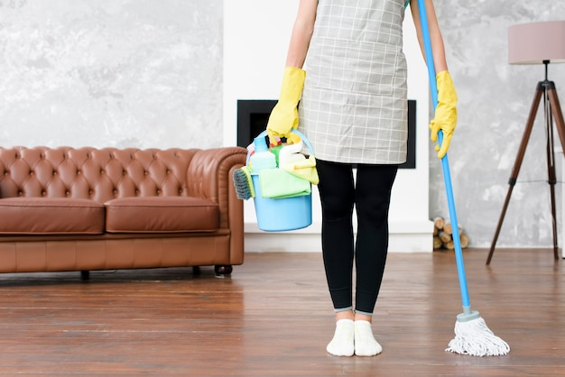 Female janitor standing at home holding cleaning products and mop in hand