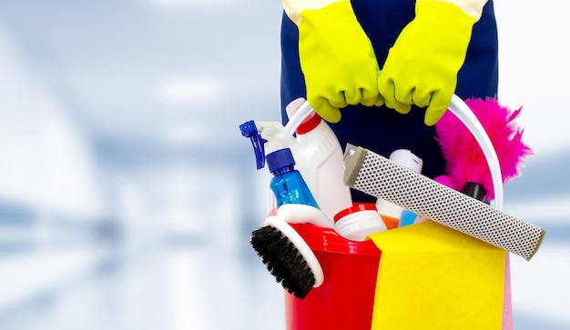 Female janitor with cleaning supplies in public building. the concept of cleaning and disinfection
