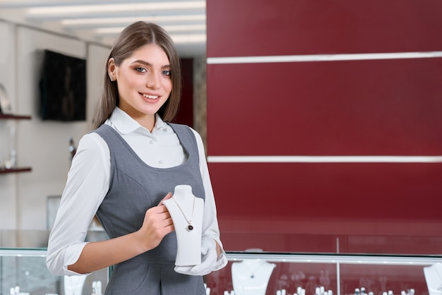 보석 가게에서 목걸이를 보여주는 동안 카메라에 미소 여성 보석 노동자
