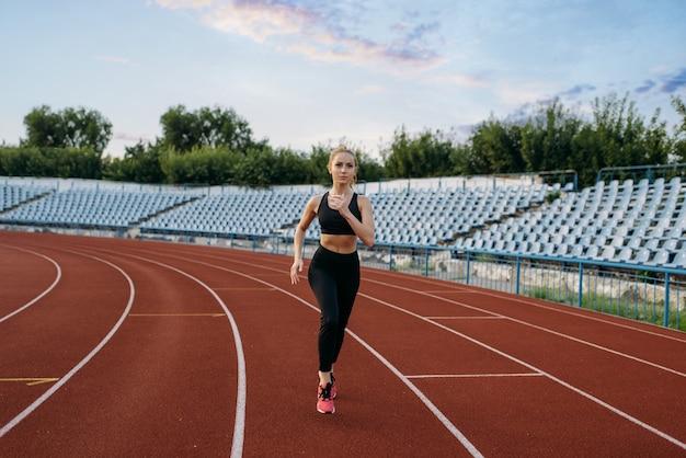 スポーツウェアのランニング、スタジアムでのトレーニングの女性ジョギング。屋外アリーナでジョギングする前にストレッチ運動をしている女性