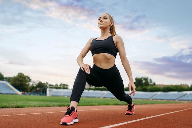 スポーツウェアの女性ジョギング、スタジアムでのトレーニング。屋外アリーナで実行する前にストレッチ運動をしている女性