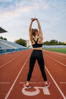 スポーツウェアの女性ジョガー、スタジアムでのトレーニング