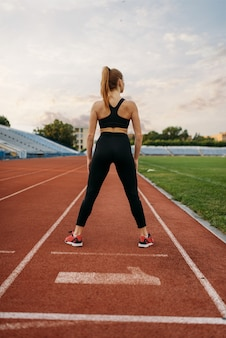 Женский бегун в спортивной одежде, тренировки на стадионе