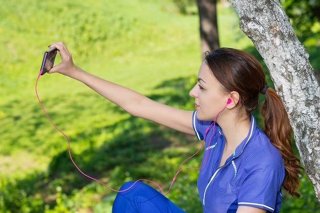 女性のジョガーは、しゃがんだ木に座って、森の中で一人でヘッドフォンで音楽を聴きながら、笑顔でスマートフォンで自分撮りをしています