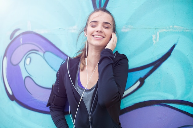 Female jogger listening music on mobile phone in front of graffiti wall