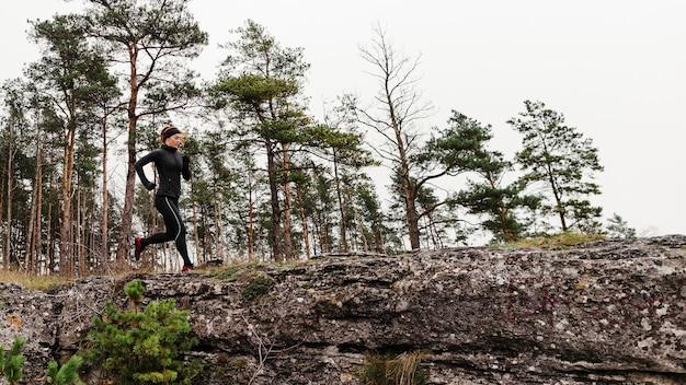 日光のロングショットで走っている女性のジョガー