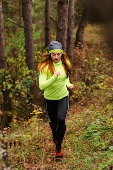 Female jogger running in the woods