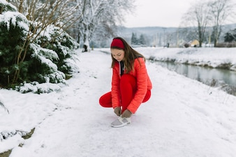 Female jogger tying shoelace near the lake in winter