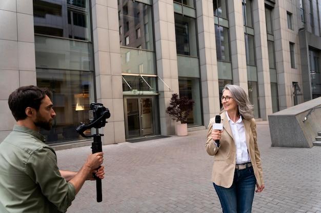 カメラマンの隣でインタビューをしている女性ジャーナリスト