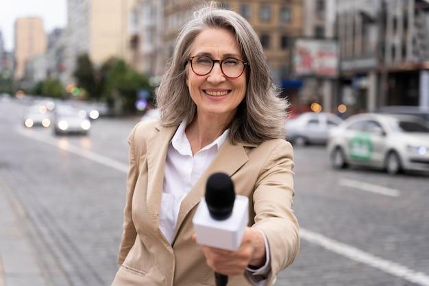 Giornalista che racconta le notizie all'aperto