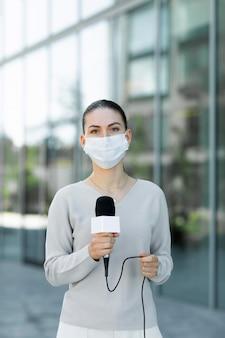 Giornalista con mascherina medica