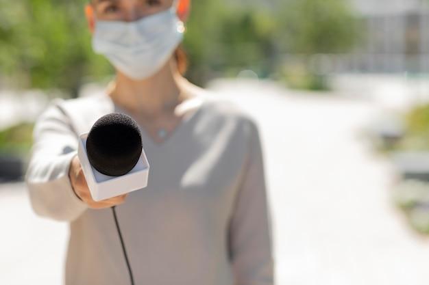 医療マスクを持つ女性ジャーナリスト