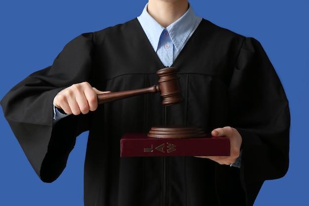 色の表面にガベルを持つ女性裁判官