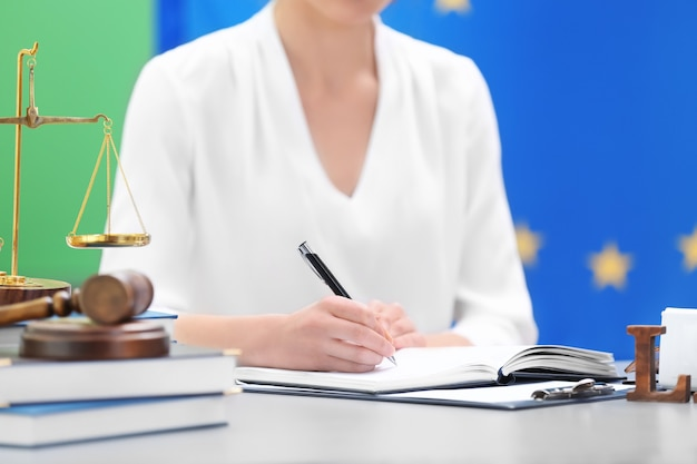 Female judge working with documents and law accessories on table