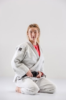 The female judokas fighter posing on gray