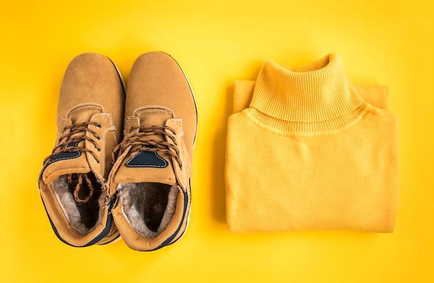 여성 점퍼와 노란색 배경에 부츠입니다. 가을 스타일. 추운 날씨를위한 따뜻한 복장. 옷 쇼핑, 판매, 유행 색상 개념 스타일