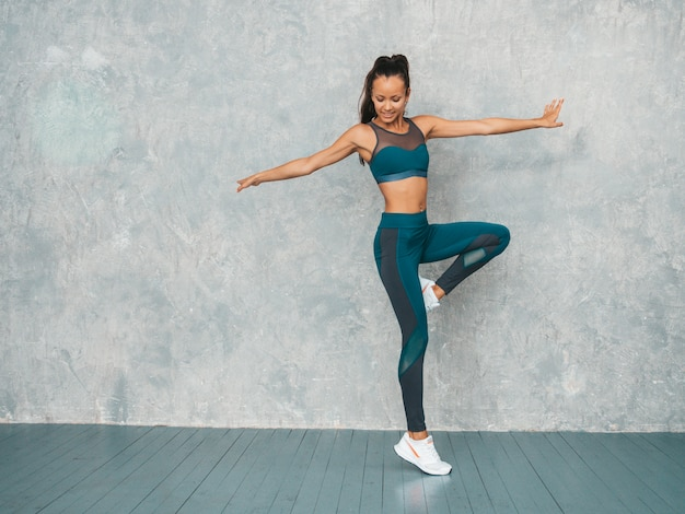Female jumping in studio near gray wall