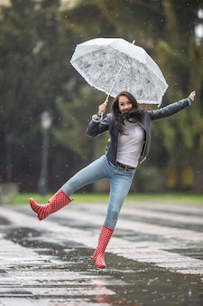 Female jumps from joy on a rainy day with an umbrella and red polka dot rain boots.