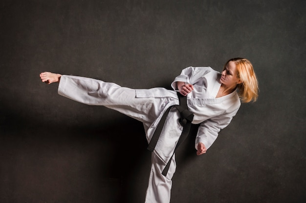 Female karate fighter kicking front view