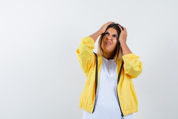 Женщина, держащая руки на голове в футболке, куртке и задумчивая, вид спереди.