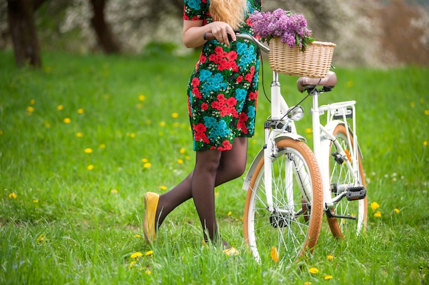 Female keeps retro white bicycle with lilac flowers