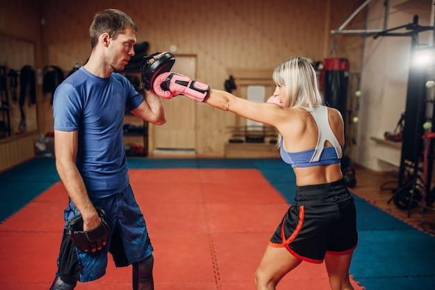 Женский кикбоксер на тренировке с личным тренером