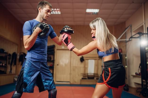 Женский кикбоксер практикует ручной удар