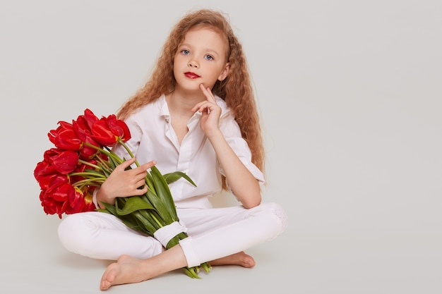 Female kid in white elegant clothing holding red tulips in hands, looking at front, keeping finger on her cheek, looks with confident expression
