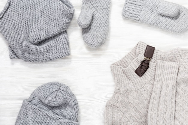 Female knitted cap, scarf, mittens and warm sweater. autumn and winter clothes for woman. top view.