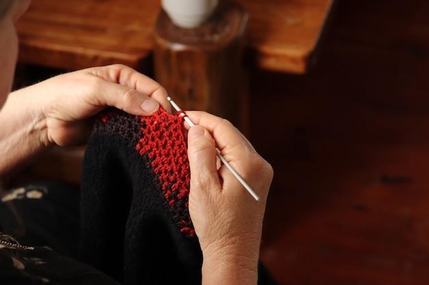 Donna che lavora a maglia un maglione