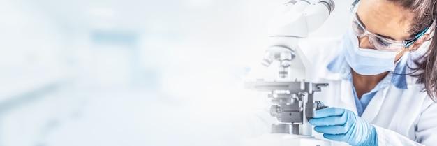 Женщина-лаборант в защитных очках, перчатках и маске сидит рядом с микроскопом и конической колбой, глядя в сторону на стол - панорамный баннер.