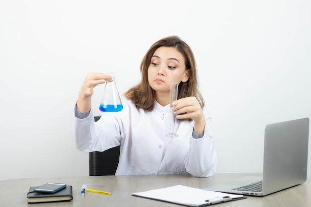 Ricercatore di laboratorio femminile seduto alla scrivania e con in mano una bottiglia di vetro medica con liquido blu.