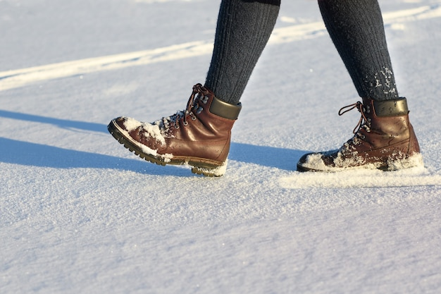 Female lags in boots walking on fresh snow in winter. closeup of winter shoes.